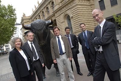 Gruppe von Menschen posiert vor der bronzenen Stierstatue der Frankfurter Börse